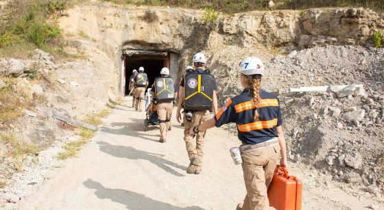 Students wearing mining equipment enter a mine set in a cliff side