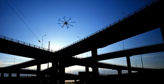 Multi-rotor drone flying next to highway bridges